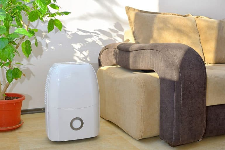 A quiet portable dehumidifier in a bedroom/living room.