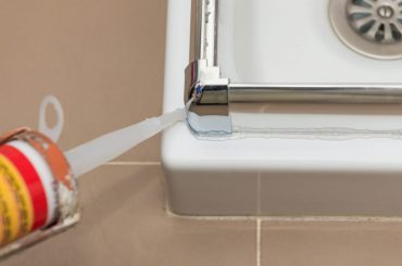 Removing silicone caulk from shower stall.