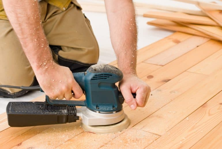 Sanding wood floors to remove paint.