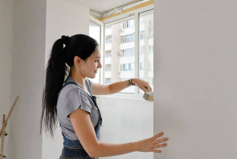 Painting a wall with a paint edger.