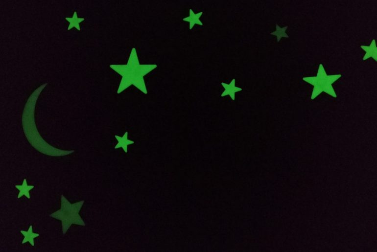 Glow in the dark stickers on a wall and ceiling.