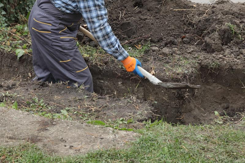 Digging a trench to divert water runoff from neighbors yard.