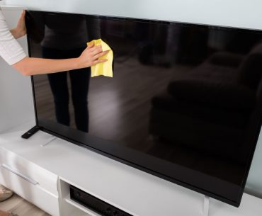 Cleaning a flat screen TV with a microfiber cloth.