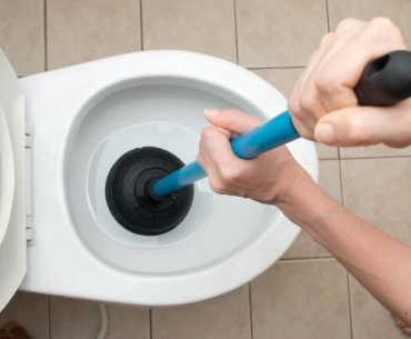 Using a plunger to unclog the toilet