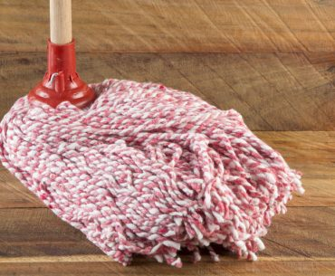 Cleaning an unfinished wood floor with a mop dipped in vinegar.