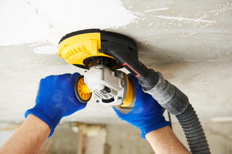 Removing paint from a concrete ceiling with a grinder.