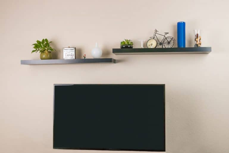 Two floating shelves and a TV installed on a wall.