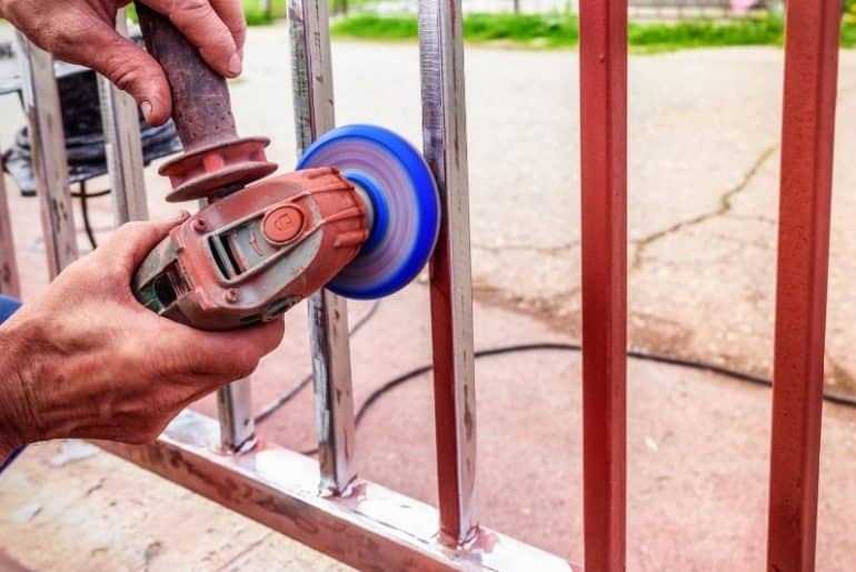 Using and angle grinder to remove paint from metal.