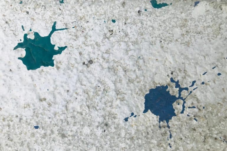 Two paint stains (blue and green) on a concrete surface that need to be removed.